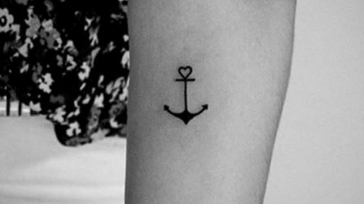 Tatuaje discreto de un ancla con un corazón.