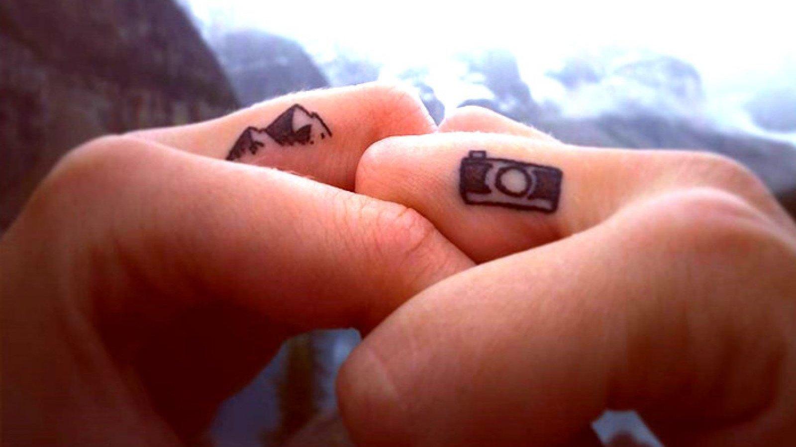 Pequeños tatuajes en el dedo de una montaña y una cámara de fotos.