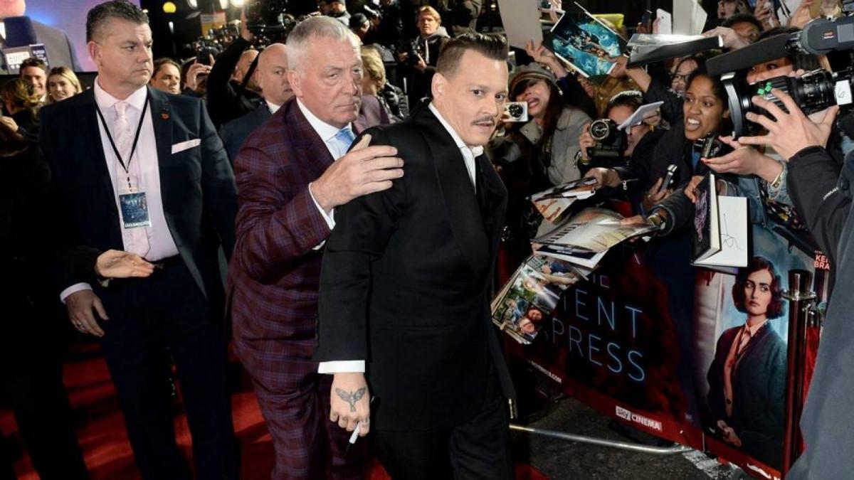 Johnny Depp es sujetado por sus guardaespaldas en el estreno de su última película.